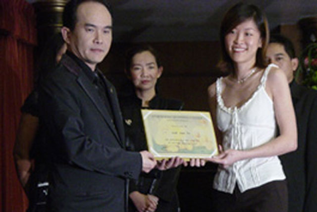 Ms Annie receiving award from Thailand's grooming school